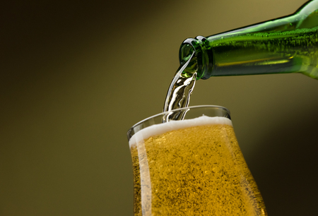 Pouring fresh beer from a bottle into a glass, alcoholic drinks and celebration concept Stock Photo