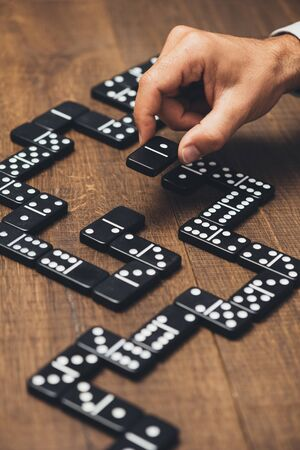Businessman playing with dominoes and holding a tile, strategy and management concept Stock Photo