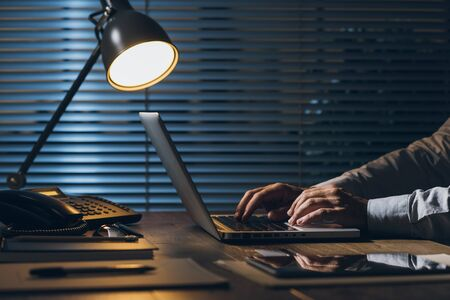 Corporate businessman working at office desk with his laptop late at night: working overtime and deadlines concept Stock Photo