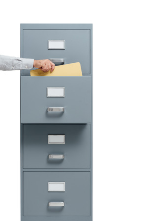 Office worker taking a file from a filing cabinet drawer, business and administration concept Stock Photo