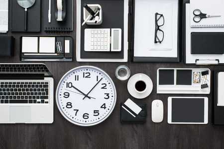 Conceptual business and management desktop with laptop, tablet, a clock and desk accessories, efficiency and time concept