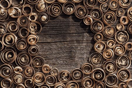 Wood spiral shavings on a vintage workbench background, blank copyspace at center: carpentry, woodworking and craftsmanship concept