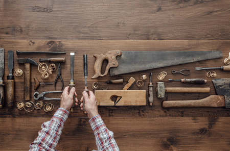 Professional carpenter holding a chisel and a gouge, flat lay collection of vintage woodworking tools on an old workbench, craftsmanship and handwork concept Foto de archivo