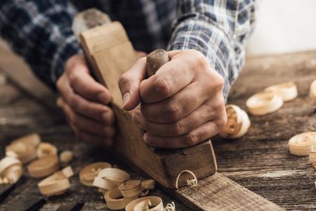 Charpentier travaillant dans son atelier, il lissera une planche de bois à l'aide d'un concept de raboteuse, de menuiserie, de menuiserie, de menuiserie et d'artisanat