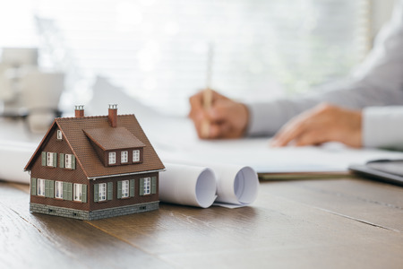 Professional architect working at office desk and drawing on a project, model house on the foreground, real estate and architecture concept