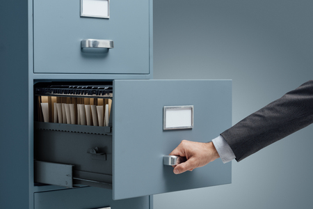 Office clerk searching files in a filing cabinet, data storage and administration concept