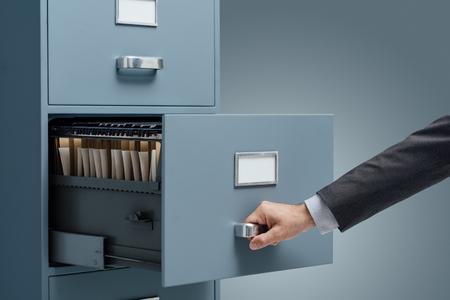 Kantoorbediende zoeken naar bestanden in een archiefkast, gegevensopslag en beheerconcept Stockfoto - 88211712