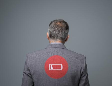 Homme d'affaires fatigué avec icône de charge faible, concept de stress et de fatigue, vue arrière