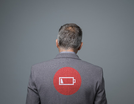 Tired businessman with low charge icon, stress and fatigue concept, back view