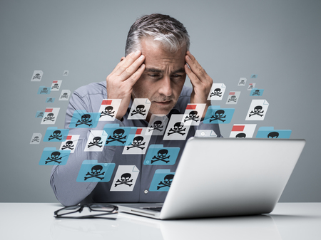 Geschäftsmann, der mit einem Computer voller Viren, infizierter Dateien und Malware arbeitet: Er ist frustriert mit dem Kopf in den Händen Standard-Bild