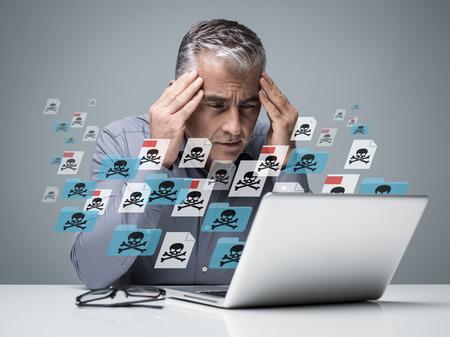 Uomo d'affari che lavora con un computer pieno di virus, file infetti e malware: è frustrato dalla testa nelle mani Archivio Fotografico