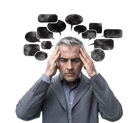 Pensive stressed man having negative thoughts and feeling confused, he is surrounded by dark speech bubbles Stockfoto