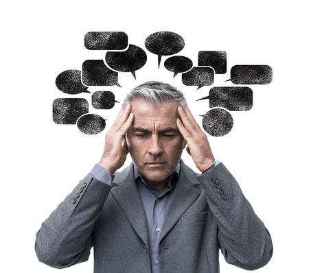Nadenkend gestrest man met negatieve gedachten en zich verward voelen, hij is omringd door donkere tekstballonnen Stockfoto
