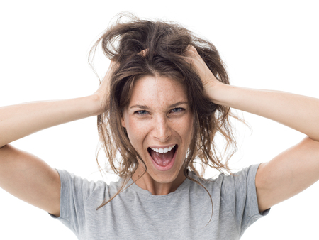 Angry stressed woman shouting and having a bad hair day, her hair is messy and tangled Stockfoto