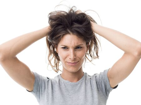 Angry stressed woman having a bad hair day, she is holding her messy and tangled hair