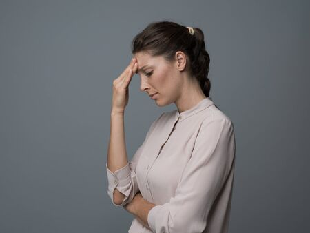 Young pensive woman feeling depressed and having a bad headache, she is touching her forehead