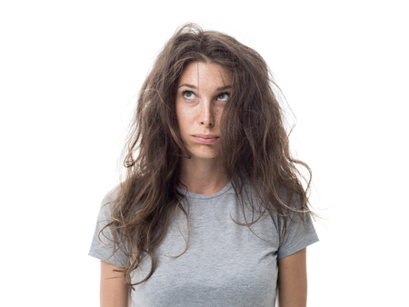 Angry young woman having a bad hair day, her long hair is messy and tangled Stockfoto