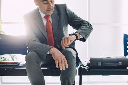 Collectieve zakenmanzitting in de wachtkamer en het controleren van de tijd, wacht hij op de vergadering Stockfoto