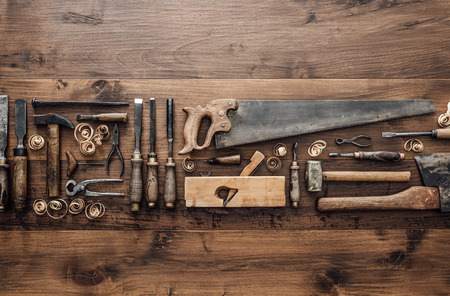 Collection of vintage woodworking tools on a rough workbench and blank copy space: carpentry, craftsmanship and handwork concept, flat lay Archivio Fotografico