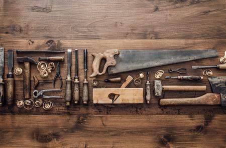 Verzameling van vintage houtbewerking tools op een ruwe werkbank en lege kopie ruimte: timmerwerk, vakmanschap en handwerk concept, plat leggen