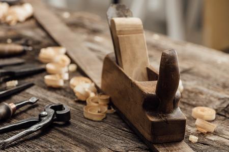 Hölzerner Hobel auf der Werkbank des Tischlers und alte Holzbearbeitungswerkzeuge, Zimmerei und Selbstkonzept