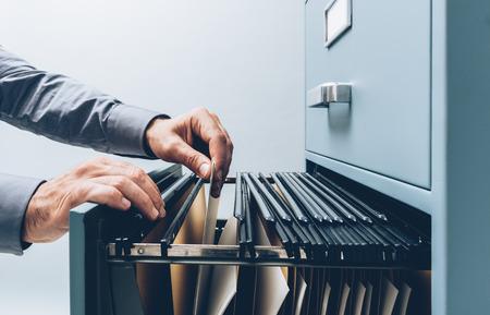 Bürokaufmann, der oben nach Dateien in einen Aktenschrankschubladenabschluß, in die Betriebswirtschaft und in das Speicherkonzept sucht Standard-Bild
