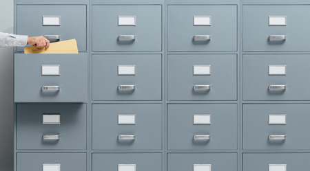 Office worker taking a file from a filing cabinet drawer, business and administration concept 스톡 콘텐츠