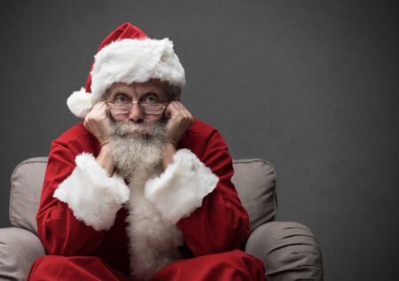 Santa Claus sitting on the armchair and waiting for Christmas, he is resting his head on his hands Archivio Fotografico