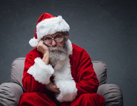 Lazy bored Santa Claus leaning on his hand and relaxing on the armchair, he is waiting for Christmas