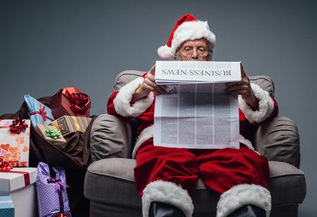 Santa Claus, die Wirtschaftsnachrichten auf einer Zeitung liest und zu Hause auf dem Lehnsessel sich entspannt