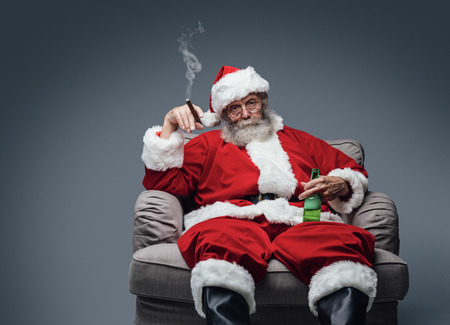 Bad Santa celebrating Christmas at home alone, he is smoking a cigar and drinking beer