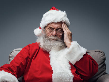 Sad Santa Claus having an headache on Chistmas Eve, stress and illness concept Stok Fotoğraf