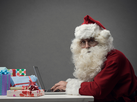 Santa Claus verbindt en werkt online met zijn laptop, hij bereidt geschenken voor en winkelt online op kerstavond