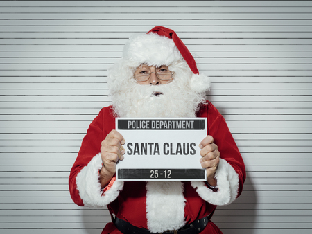 Santa Claus arrested on Christmas eve, he is posing for his mug shot at the police department and holding an identification board