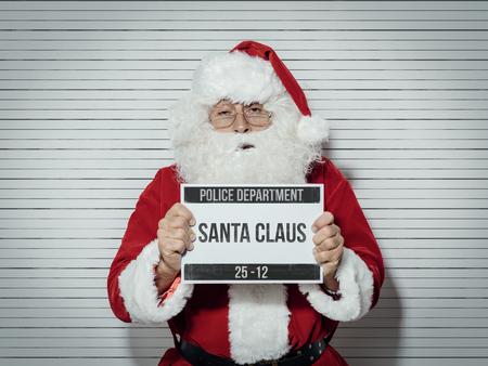 Papai Noel preso na véspera de Natal, ele está posando para sua foto no departamento de polícia e segurando uma placa de identificação