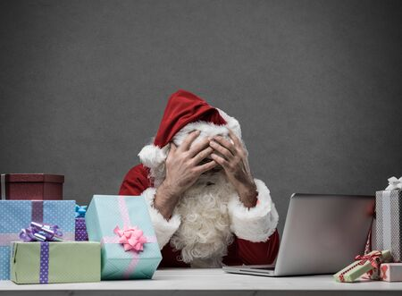 Stressed frustrated Santa Claus with head in hands  connecting with his laptop, he is having computer problems on Christmas Eve