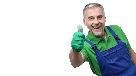 Happy professional gardener with green gloves giving a thumbs up