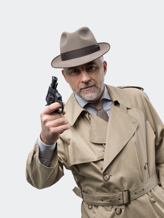 Retro spy agent pointing a gun, he is wearing a trench coat and a hat Banque d'images