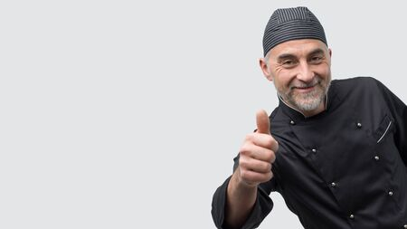Successful mature chef posing with thumbs up and looking at camera