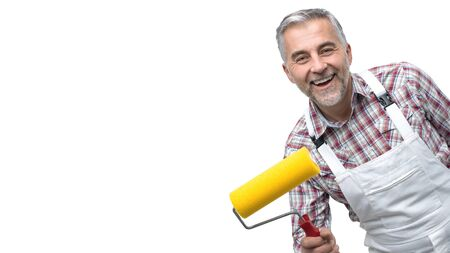 Smiling professional painter posing with roller paint, home repair concept