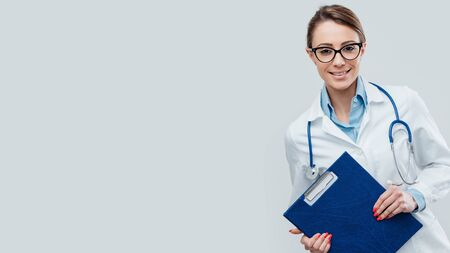 Confident young female doctor smiling and posing with clipboard and stethoscope