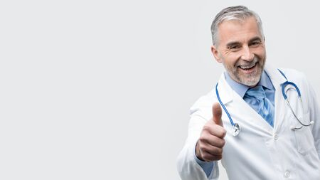 Confident smiling mature doctor posing and giving a thumbs up