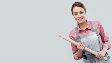Young smiling housewife posing with rolling pin and apron