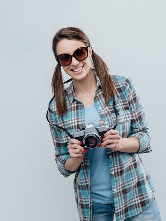 Smiling female photographer and tourist, she is posing and holding a digital camera