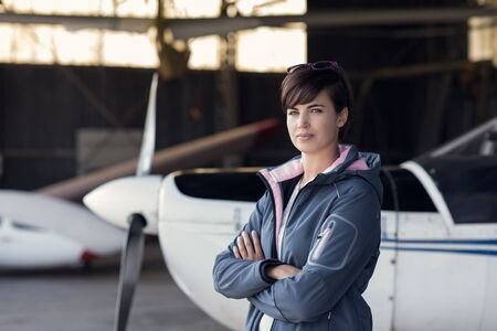 Beautiful woman posing in the hangar with arms crossed, light aircraft in the background