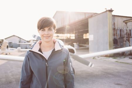 Smiling cheerful woman posing at the airport with light aircraft and hangar on the background, she is a young pilot Banque d'images