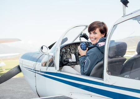 軽飛行機のコックピットにメスの操縦者の笑みを浮かべて、彼女はアビエイター ヘッドセットを保持しているとカメラ目線 写真素材