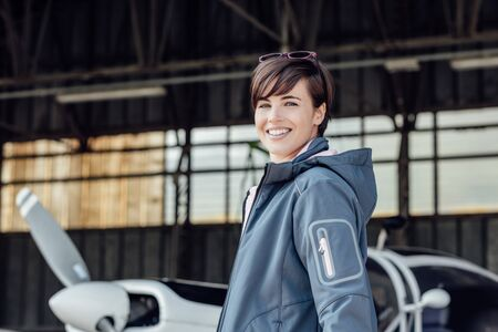 Cheerful smiling young woman posing in the airport hangar with her private small aircraft, travel and aviation concept