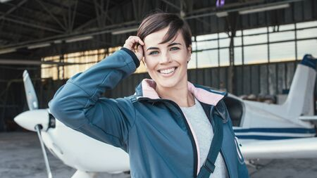 Smiling female pilot posing in the airport hangar, propeller airplane on the background, travel and aviation concept