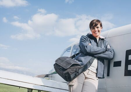 Smiling cheerful female pilot leaning on a propeller airplane and posing, blue sky on the background, travel and aviation concept Banque d'images